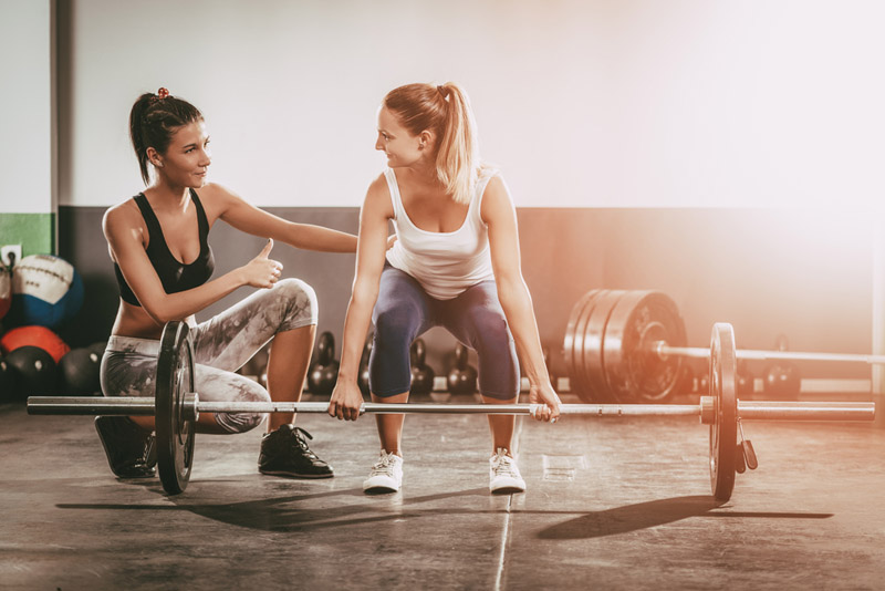 Woman exercising with female fitness trainer