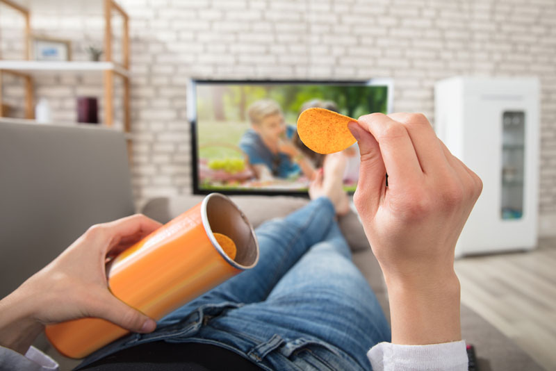 Woman eating chips while watching television